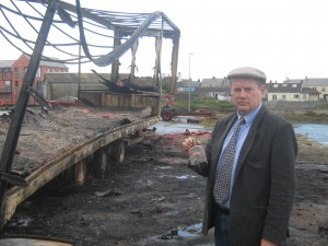 Cllr Cadogan Enright holding vodka bottle, with burnt shipping containers from whence hundred of fish boxes were set alight